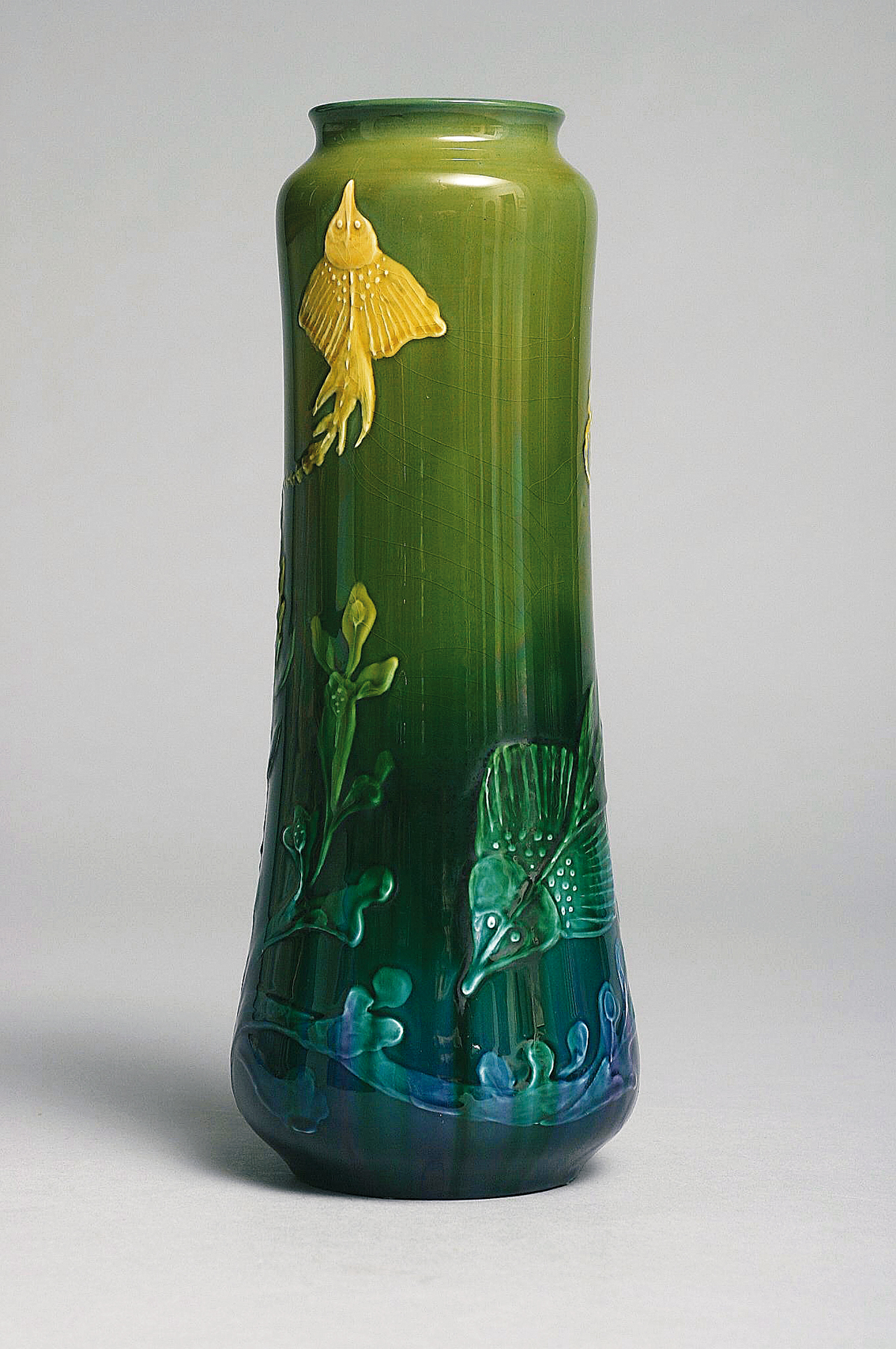 An art-nouveau vase decorated with ray fish within underwater landscape
