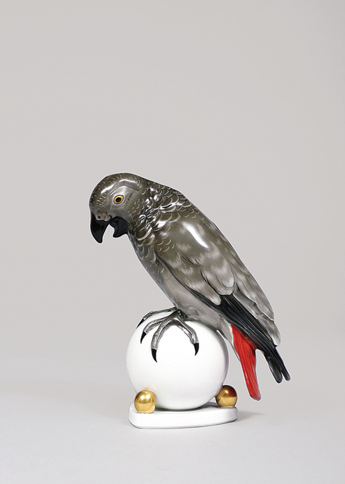 An animal figure of a grey parrot seated on a ball