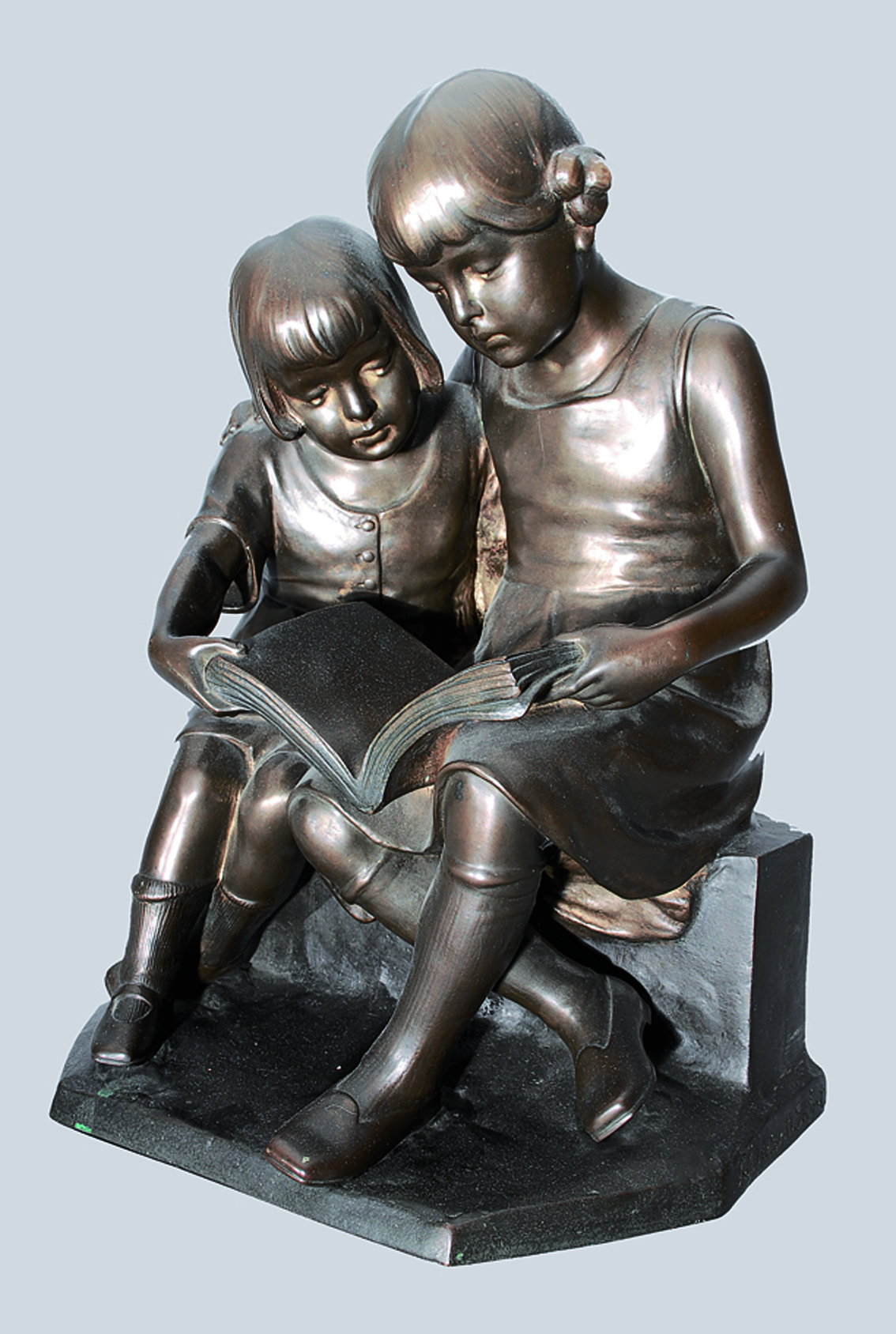 A bronze figure of reading children