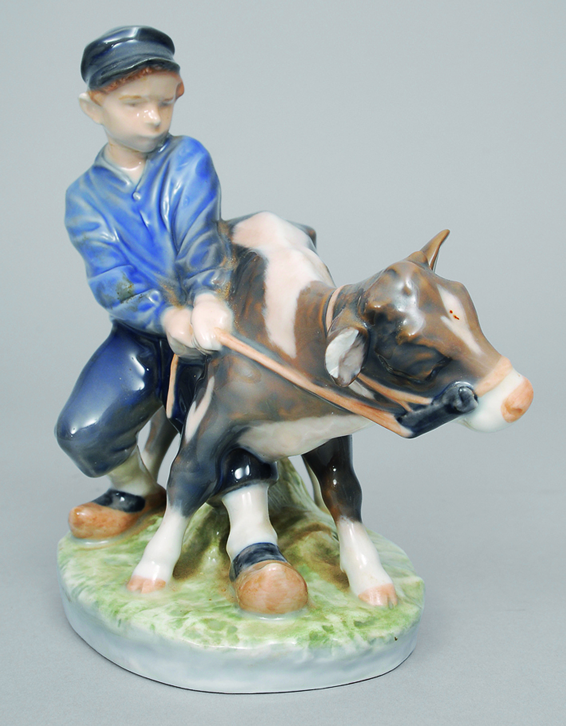 A figure of a boy with a cow