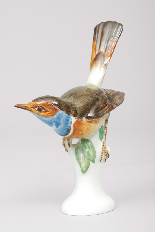 An animal figurine 'bluethroat seated on a branch base'