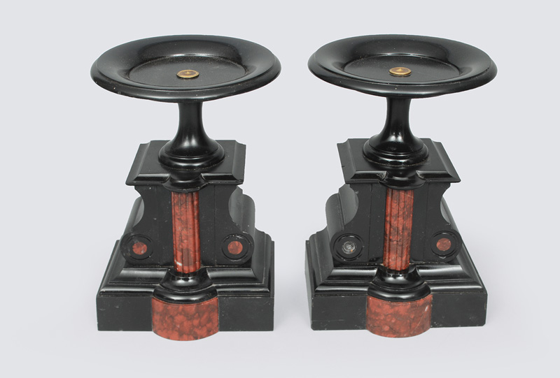 A pair of black fireplace consoles