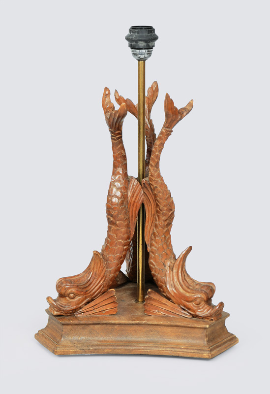 A wooden lamp stand with dolphin decor