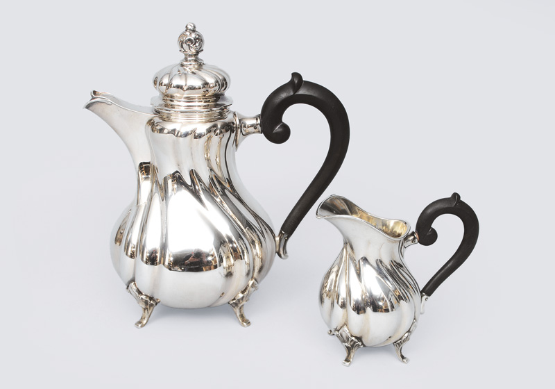 A coffee pot and creamer in style of Chippendale