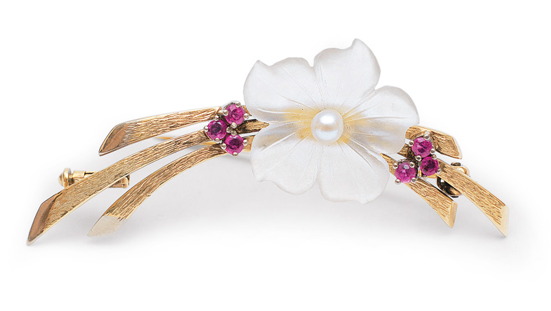 A petite flowerbrooch with small rubies