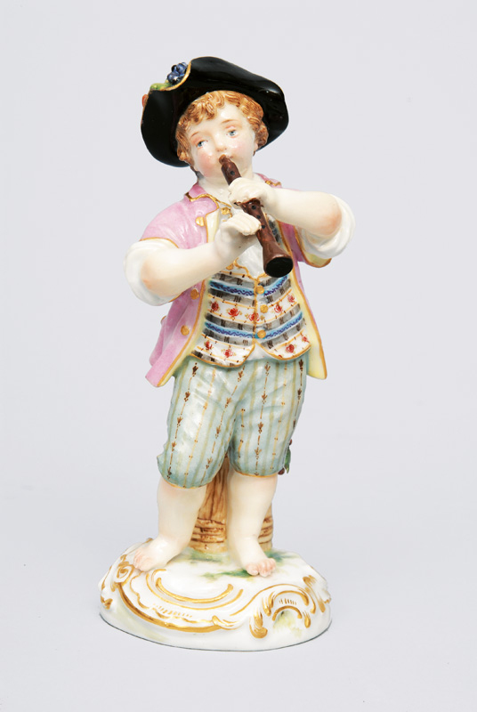 "A figurine ""Gardener""s child playing the flute"""