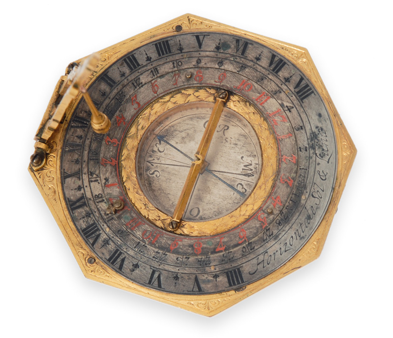 A sun and moon dial with compass