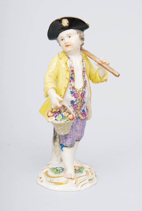 "A figurine ""Gardener""s child with hoe and flower basket"