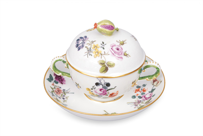 A small tureen on saucer decorated with flower pattern