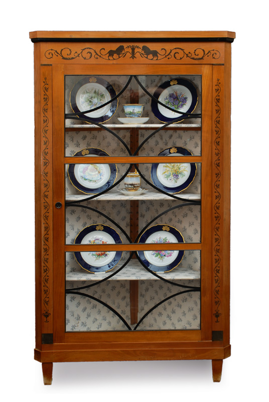 A corner glass cabinet with black stain friezes