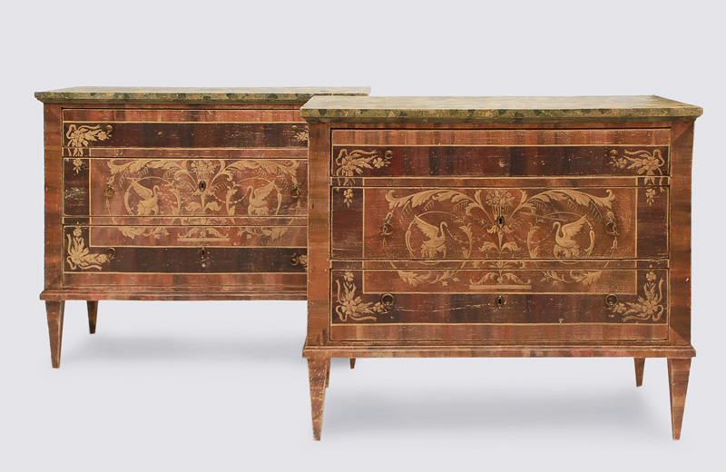 A pair of Louis Seize chest of drawers with ornaments of swans and vases