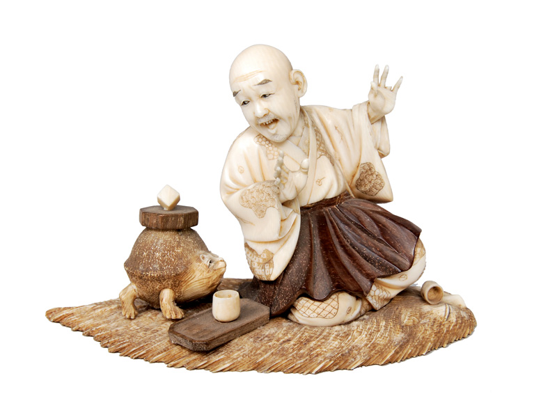 An okimono - Sitting monk drinking tea