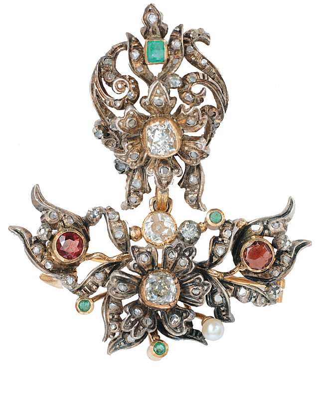 An antique flower brooch with diamonds and emeralds