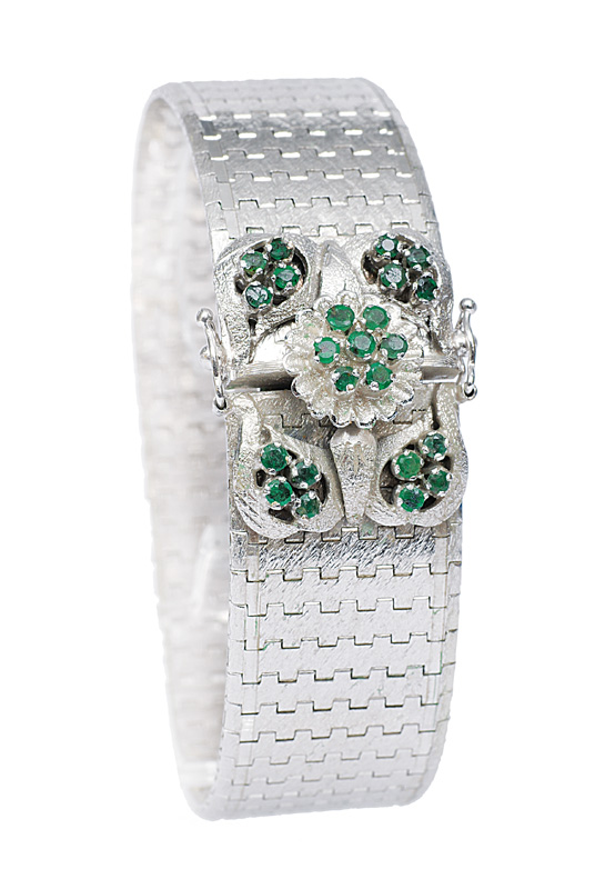 A white gold bracelet with emerald clasp