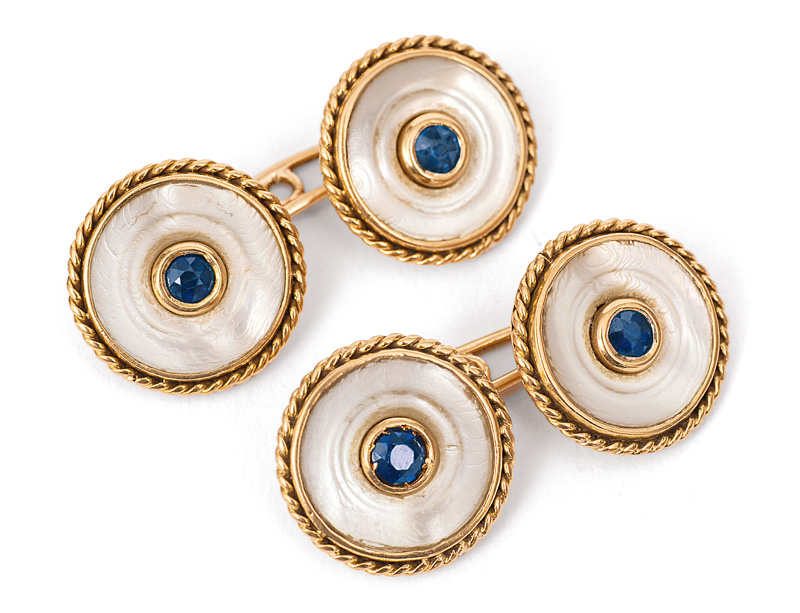 A pair of cuff links with mother-of-pearl and sapphires