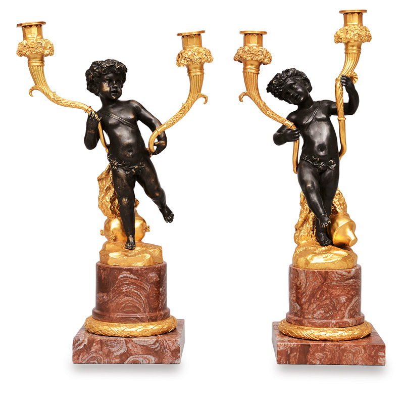 A couple of candleholders with putti