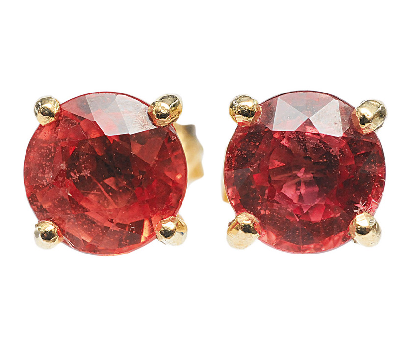 A pair of earstuds and matching ring with padparadscha sapphire