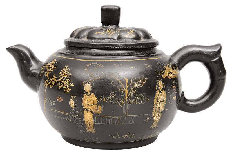 A black lacquered tea pot with fine gold decoration