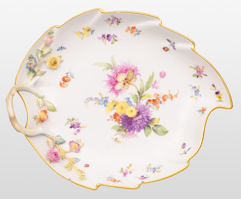 A leaf shape bowl with plastical flowers