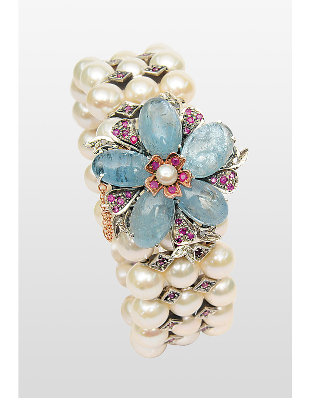 A pearl bracelet with aquamarine and ruby clasp