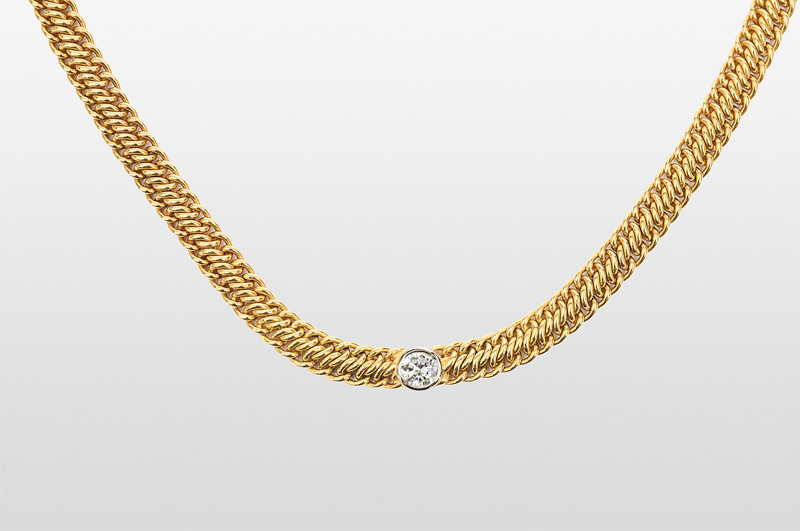 A golden necklace with one diamond