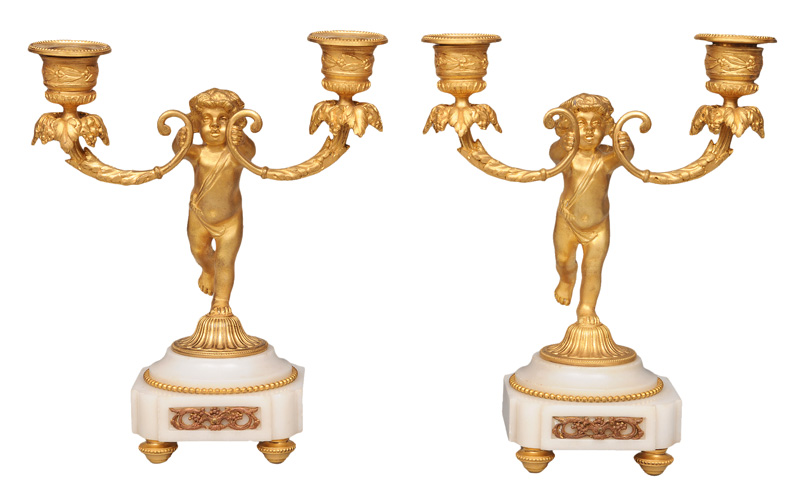 A pair of bronze and onyx candle holders with putto