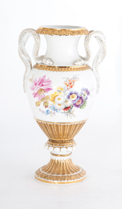 A vase with snake handles and flower bouquets