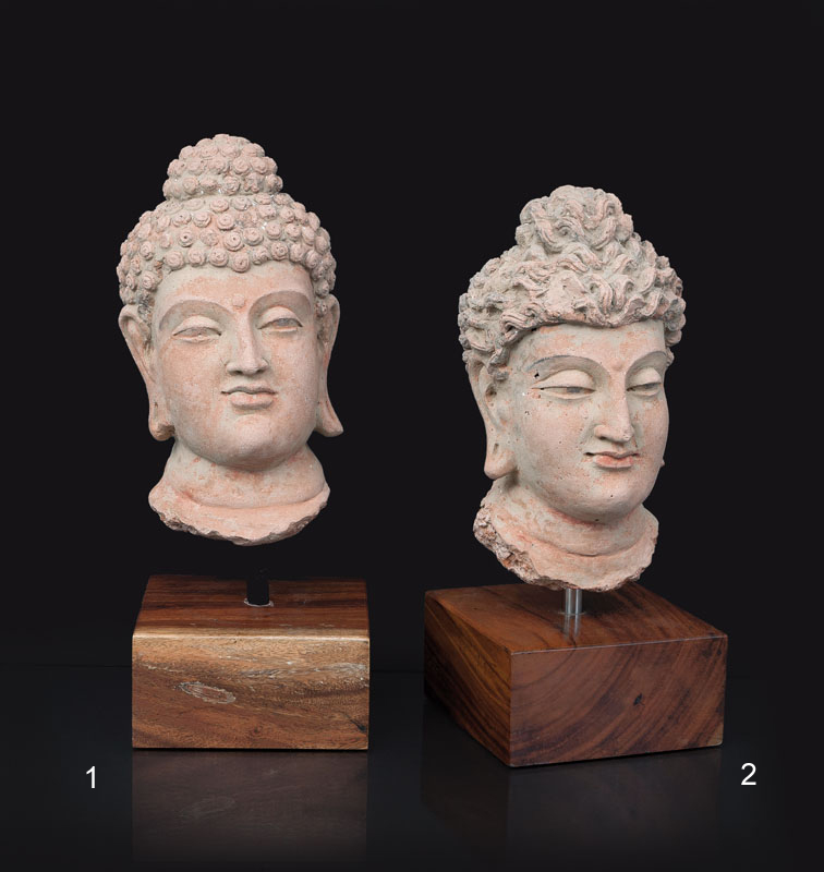A terracotta head of a buddha with curled hair