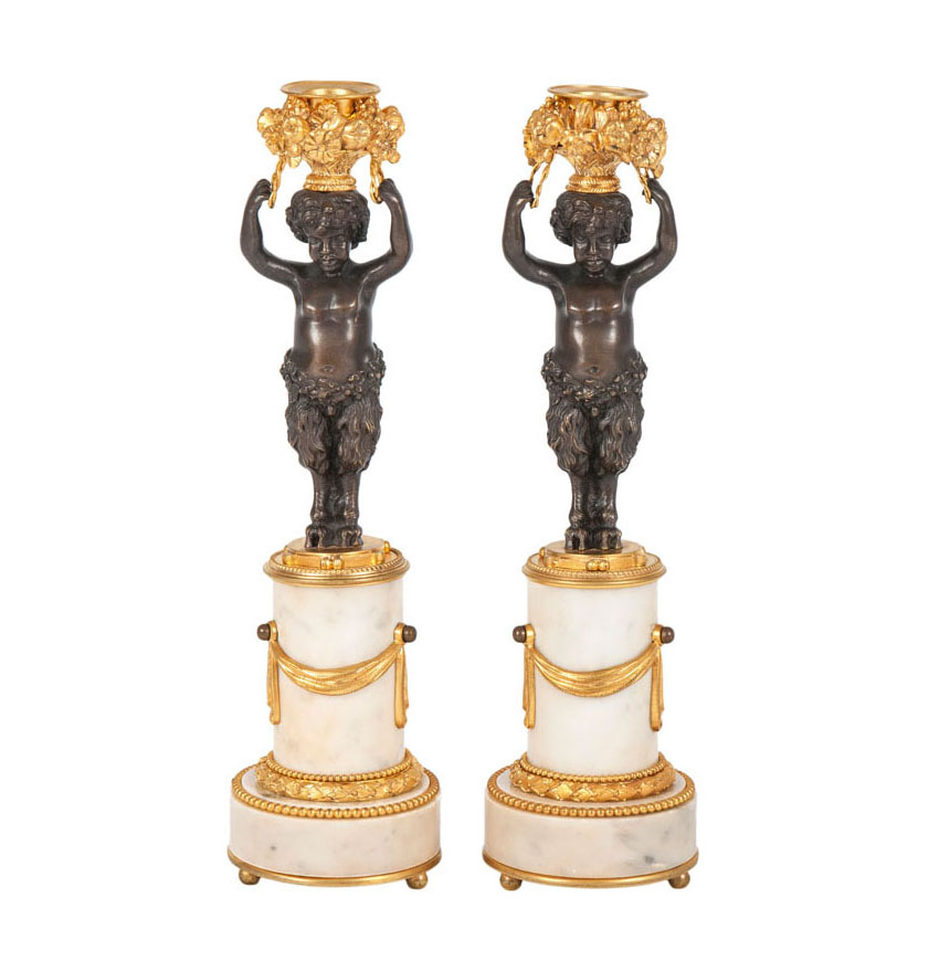 A pair of bronze candlesticks with small satyr-figure