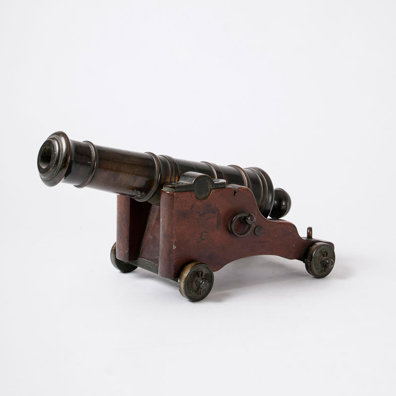 A miniature ship cannon on a wooden carriage