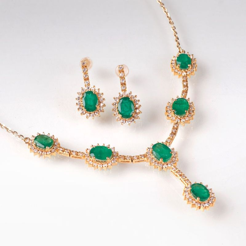 An elegant emerald diamond necklace with a pair of earrings