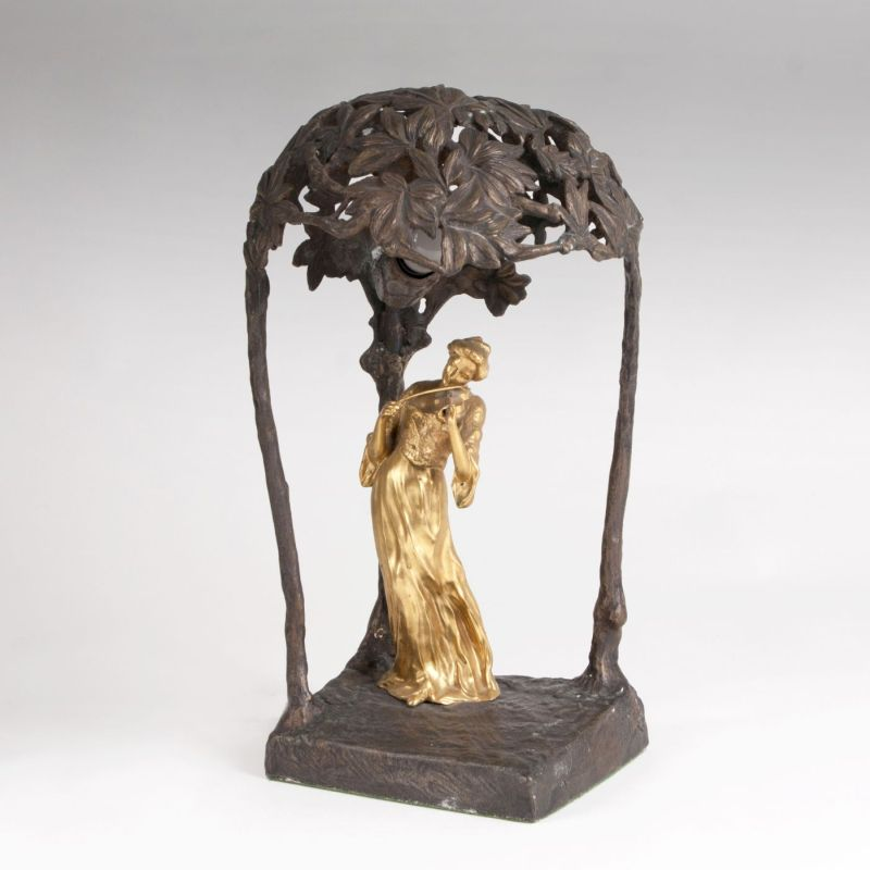 An Art Nouveau table lamp with a female violinist