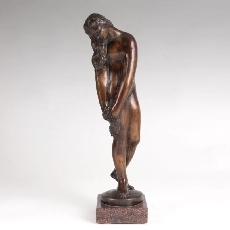 A bronze figure of a female nude holding a cloth