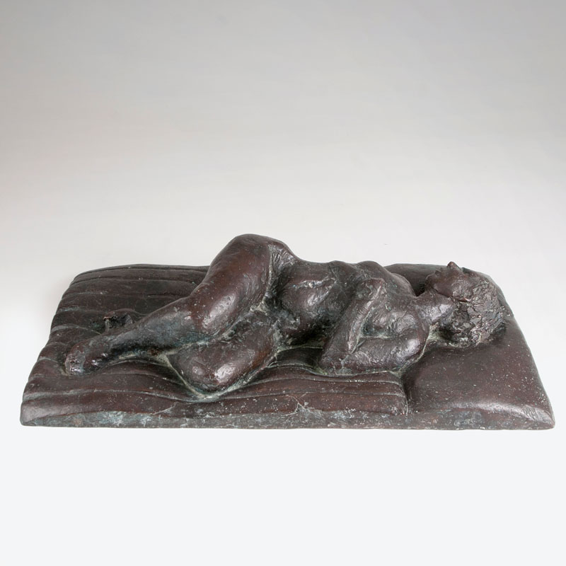 A bronze sculpture 'Reclining female nude on a mattress'