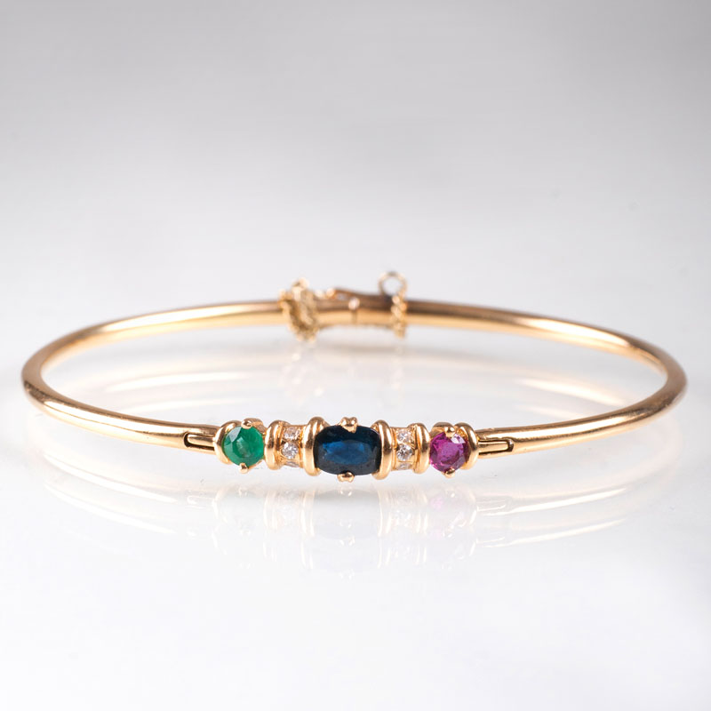 A petite golden bangle bracelet with precious stones