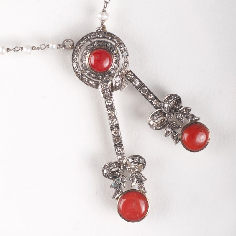 A coral diamond pendant with pearl necklace