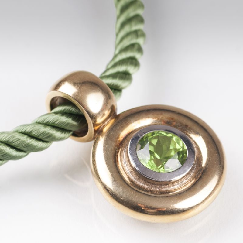 A golden pendant with peridot and two cord necklaces