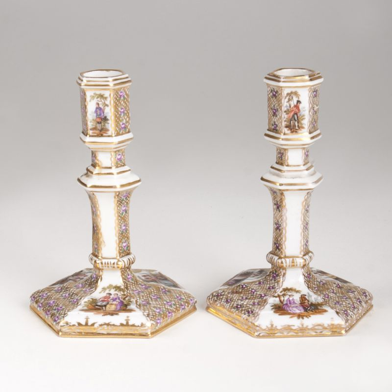 A pair of porcelain candlesticks with Watteau scenes