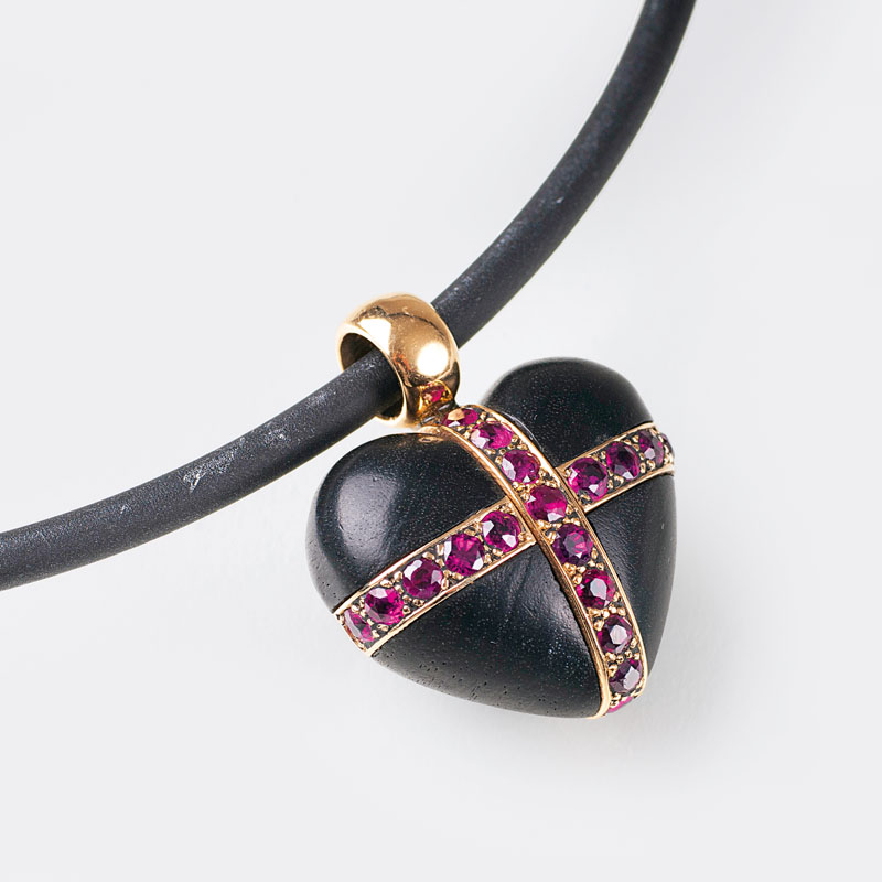 A heart shaped wood pendant with rubies