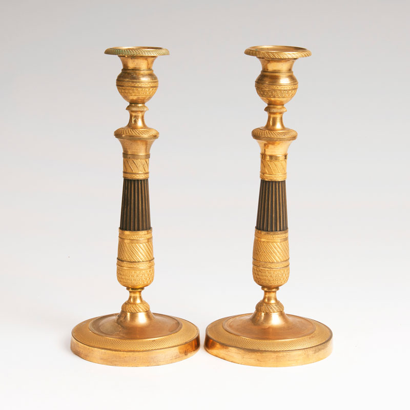 A pair of firegilt Empire candlesticks