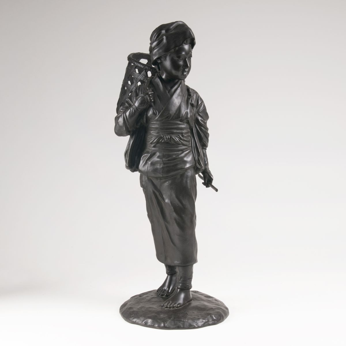 A Japanese bronze sculpture 'Boy with pannier'