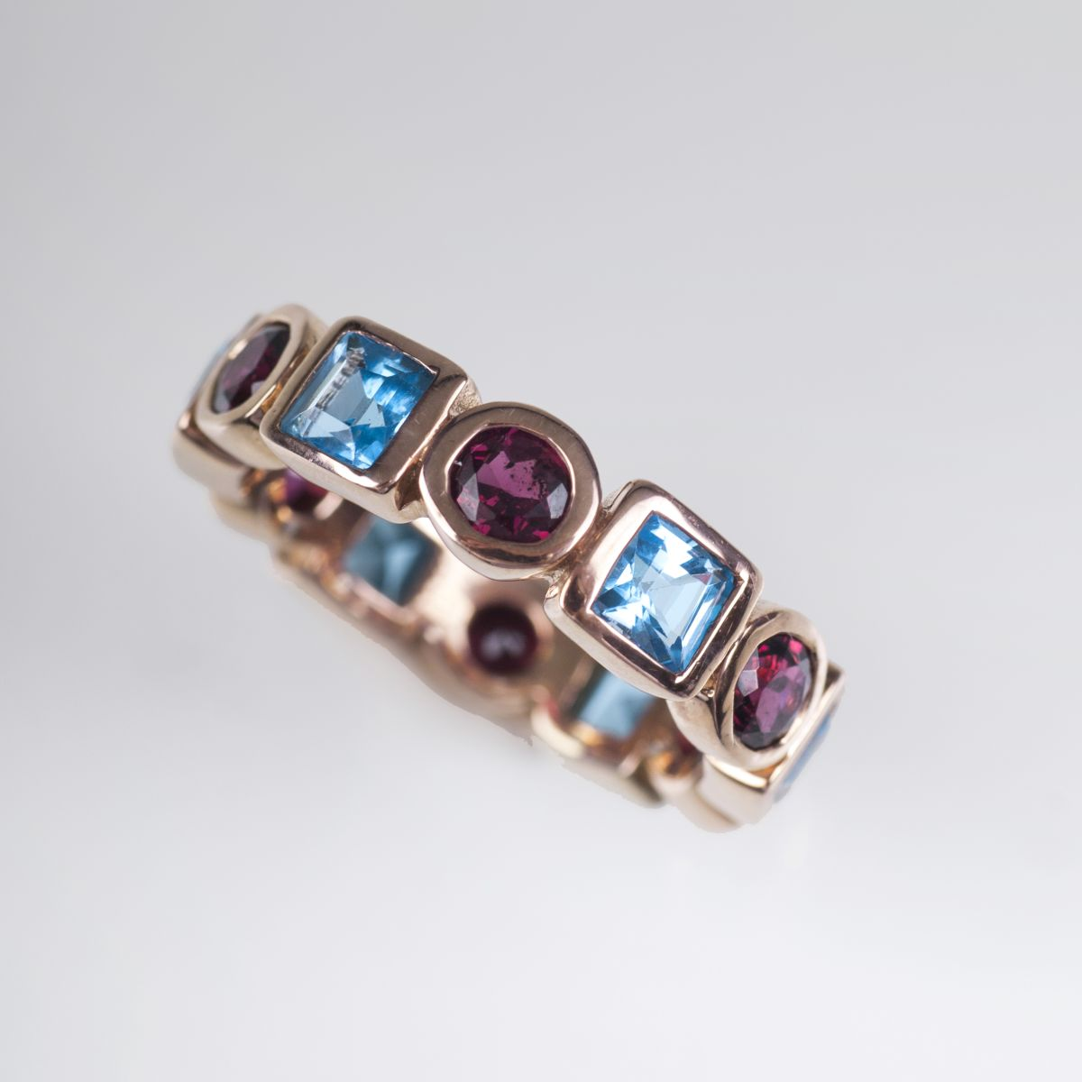 A memory ring with blue topaz and garnet