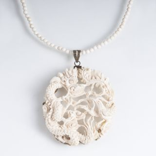 An antique ivory pendant 'Dragon and Phoenix'
