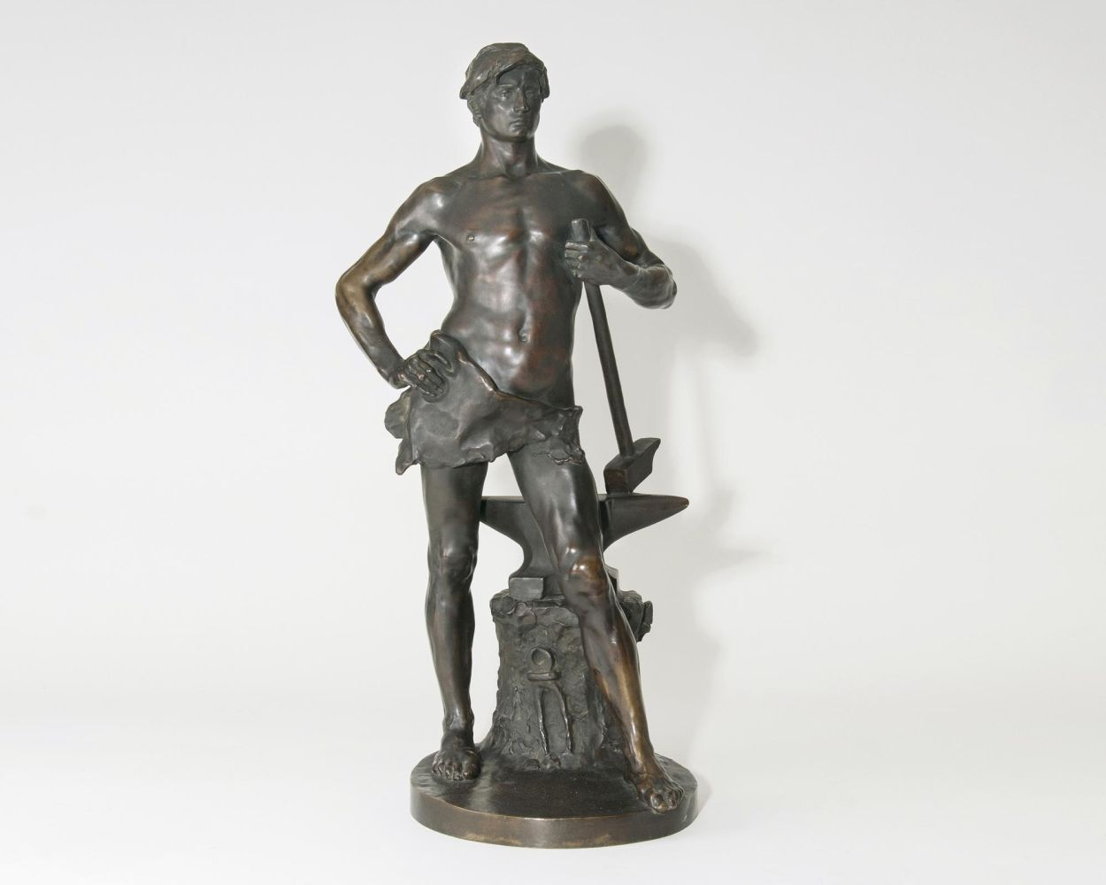 A Large Figure  'Blacksmith standing beside a tree trunk with an anvil, holding a mallet'